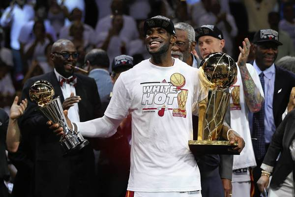 LeBron James of the Miami Heat holds trophies after Miami defeated the San Antonio Spurs 95-88 to win Game 7 of the 2013 NBA Finals.