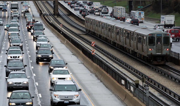 A CTA Blue Line train moves past both inbound and outbound Kennedy Expressway traffic in Chicago.