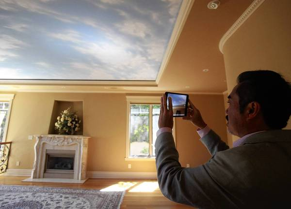 A real estate agent takes video of a house in Seattle for which he'll narrate in Chinese and provide to potential buyers in China. Investors purchased 24 percent of all existing homes sold last year, according to the National Association of Realtors.