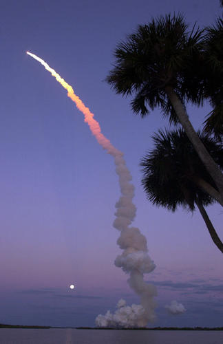 Space Shuttle Atlantis streaks past a full moon on its way to the International Space Station Alpha.