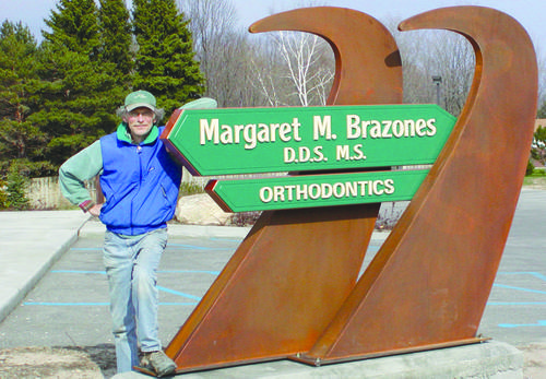 Boyne City sign artist Bruce Janssen shows off one of his masterpieces, which also shows how strong his influence can be seen throughout Charlevoix and Emmet counties.