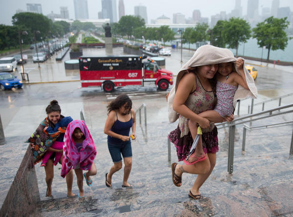 Rain douses Chicago resident Jimena Flores (under towel), as she carries family member Valentina Chavez into the Planetarium on Friday. She is followed by other family members.