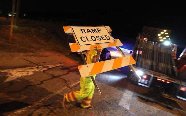 A worker carries a sign as officials close down the Moraga Drive ramp to the northbound 405 as construction crews begin their work in the Sepulveda Pass in September.