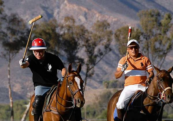 Chris Erksine, left, upon Leon, gets a polo lesson from a patient Alvaro Tadeo at the Temecula Valley Polo Club.