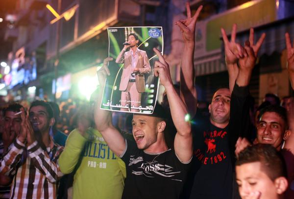 "A Palestinian holds a picture of Muhammad Assaf, a Palestinian finalist on the ""Arab Idol"" talent show, as fans watch his televised performance in the West Bank city of Ramallah."