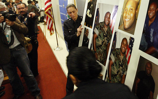 LAPD personnel display pictures of Christopher Dorner during a news conference at LAPD headquarters in Los Angeles.