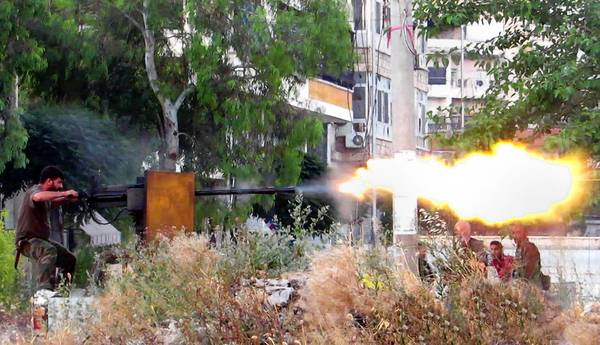 A photo taken by a Syrian citizen shows a rebel firing a heavy machine gun toward government forces in Aleppo. Members of the opposition have secretly been receiving weapons training from the U.S.