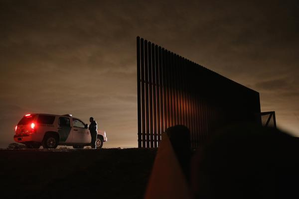 Border Patrol agent Sal De Leon speaks with fellow agents near a section of U.S.-Mexico border fence on April 10, 2013 in La Joya, Texas.