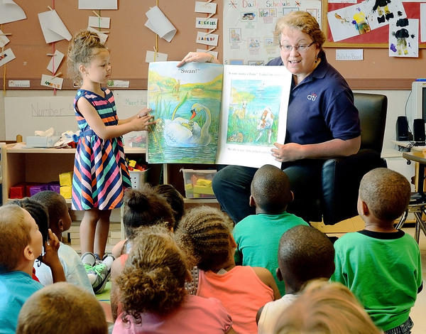 Ja'seri Chapman, left, helps Citi's Ellen Prete with an ovesized book as Prete reads to children at Head Start Friday. United Way & Citi partnered to provide literacy kits and books in support of Day of Action and Summer Learning Day.
