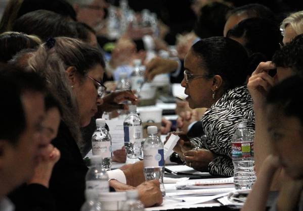 Job seeker Yerusalem Gizaw Ashenafi, center, asks questions about how to polish her resume during the 2013 Anaheim OC Job Fair and Expo this week. About 5,000 people attended the event.