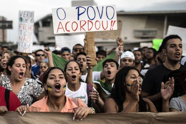 "Residents of the upper-middle-class neighborhood of Barra da Tijuca, in Rio de Janeiro, shout slogans as one holds up a sign reading, ""The people woke up."""