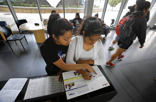 Luz Portillo, 21, left, helps her 14-year-old sister, Jocelyn Portillo, who goes to high school, register for a college-level Spanish I course at Harbor College. They learned the class was already full but hoped to crash it.