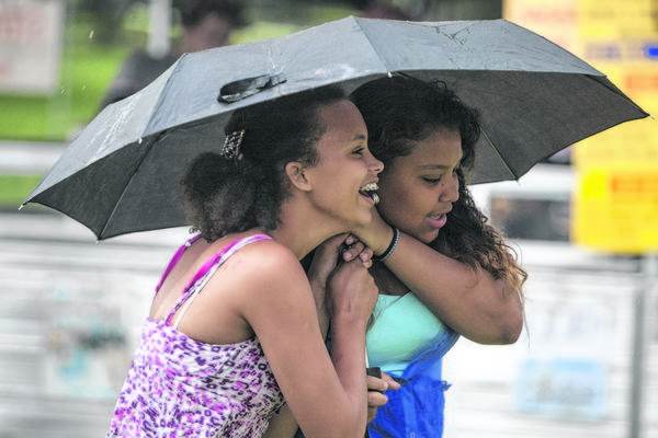 Friends Savonnah Fox, 14, left, and Antonia Martinez, 14, huddle together under an umbrella as a steady rain begins to fall during Mishawaka Summerfest on Friday at Merrifield Park in Mishawaka.