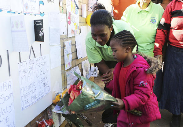 A girl places flowers next to the 'Get Well' messages outside the hospital where former South African President Nelson Mandela is being treated in Pretoria.