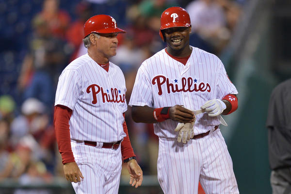 Ryan Howard laughs with Phillies third base coach Ryne Sandberg after hitting a triple against the Nationals.