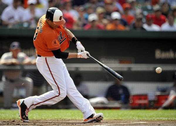 The Orioles' Manny Machado hits a one-run double in the first inning against the Red Sox.