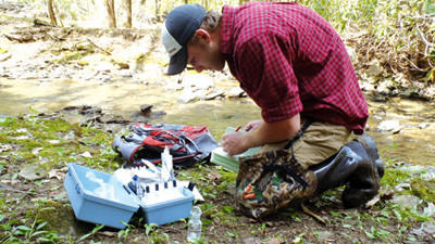 Drew Walker, student intern for the Somerset Conservation District, takes water samples of the North Fork of Bens Creek.