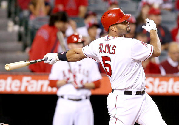 Angels' Albert Pujols hits a solo home run against the Seattle Mariners.