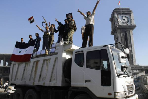Forces loyal to the Syrian army celebrate as they drive through the main square of Qusair after helping President Bashar Assad's soldiers retake control of the area this month.
