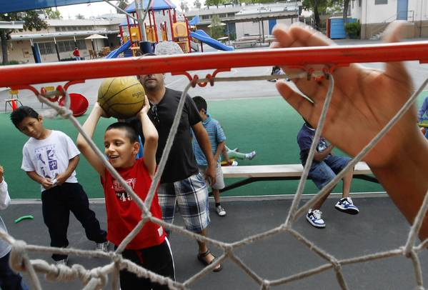 At Frances Blend school, a teacher bangs on a hoop rim to help a visually impaired third-grader shoot for the basket.