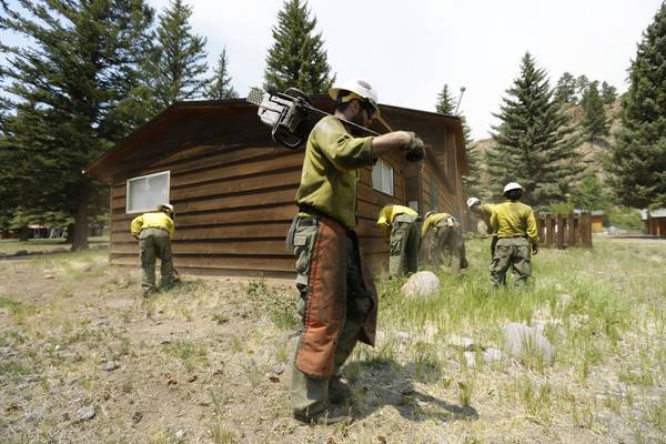Fire crews clear brush near structures in South Fork, Colo., as another fast-burning wildfire threatens a mountain tourist enclave.