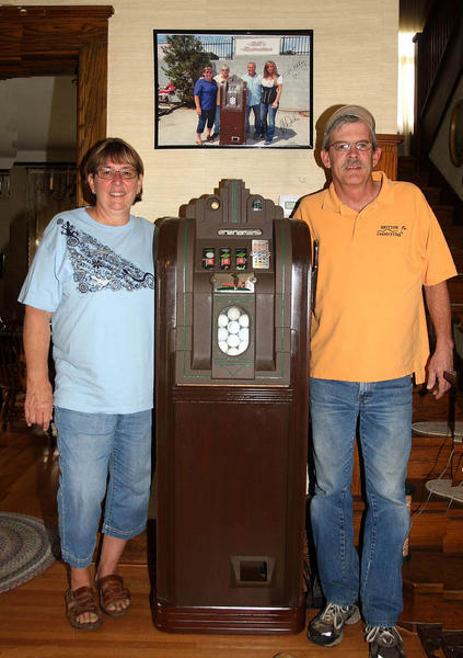 "Ulic Henehan, right, and his fiancee, Rosanne Miller, took a rare golf ball-dispensing slot machine to Las Vegas, where it was restored and featured on a recent episode of the History Channel's ""American Restoration."" On the wall above is a photo of Henehan and Miller with the stars of the show."