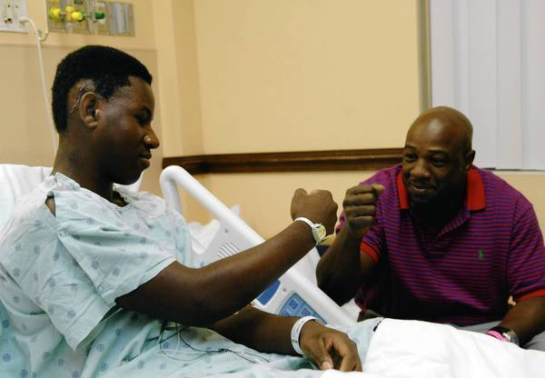 Brandon Reid, 15, trades a fist bump with his dad, Marvin Reid, while recovering from a gunshot wound to the head. He was in his mother's apartment in Miramar Thursday night celebrating the Miami Heat's win when a stray bullet hit him behind his right ear.