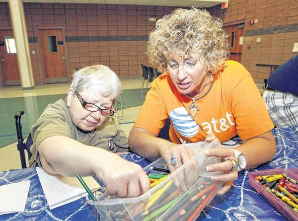 Judy Nemeth, left, gets help searching for a colored pencil from Carri Hall Reeves, president of the South Bend council of the AT&T Pioneers, at the Corvilla art therapy session at Litle Flower Catholic Church. AT&T has provided a $5,000 grant to support the art program for the Corvilla residents.
