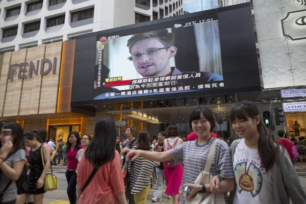 Edward Snowden is shown during a local news program displayed on a giant monitor on a building in Hong Kong.