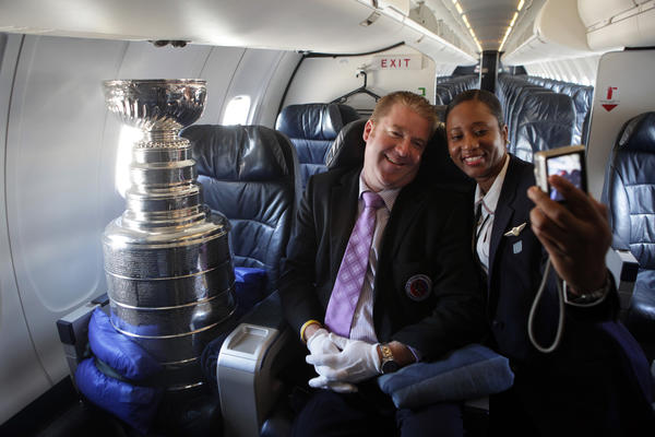 Mike Bolt, Keeper of the Cup, poses with flight attendant Marsha Sappleton after it returned back in Chicagoin 2010, engraved with all the Blackhawks names.