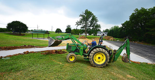 George Morris, a maintenance worker for the Martinsburg-Berkeley County Parks & Recreation Board, grades a path for a new sidewalk Thursday at Ambrose Park in Martinsburg, W.Va. New pavilions, a parking lot and a dog park are among improvements planned for the park.