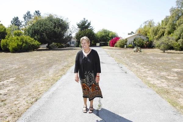 Kathy Anderson walks down her Tustin Avenue home's original driveway as she recalls living on the 1.24-acre property in Costa Mesa for nearly her entire life. The land is set to be subdivided into 14 homes.