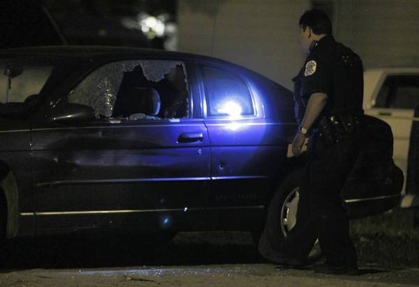 Chicago police examine a car damaged in a shooting Sunday in the 10900 block of South Throop Street that left one person wounded.