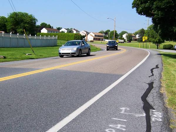 A layer of specially formulated aggregate material is basically glued to the road to increase wet-road skid resistance on sharp curves where frequent crashes occur. This is a portion of Schadt Avenue, west of MacArthur Road, in Whitehall Township.