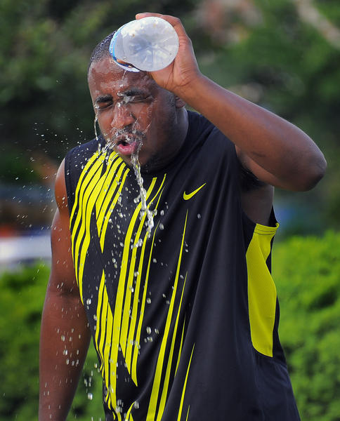Mance Walls, III, who attended Woodlawn High and will be a freshman at Merrimack College (Mass.) pours water on his face during summer break, training for football at Rash Field in the Inner Harbor.