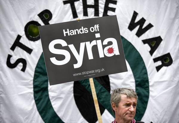 A man holds a placard during a demonstration against Western involvement in the Syria conflict outside the U.S. embassy in London on June 15. What happens in Syria, where President Obama has pledged to provide weapons to anti-government forces in that country, is one factor among many that will help determine the president's legacy.