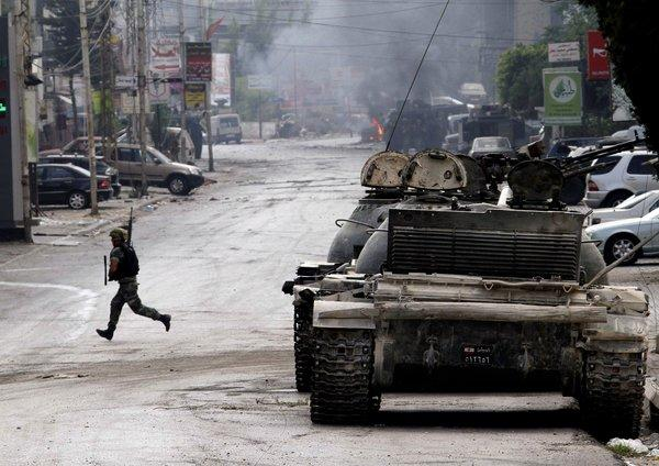 A Lebanese soldier runs across a street during clashes in the southern port city of Sidon.