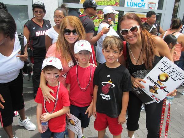 Las venezolanas Patricia Meredith (izq.) y Mayeln Villar posan con sus hijos durante el desfile de los campeones de la NBA, Heat de Miami, el 24 de junio de 2013 frente a la American Airlines Arena