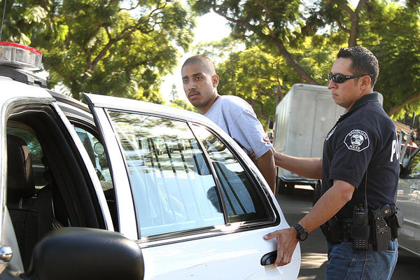 A bill moving through the Legislature would require law enforcement officials to notify minors and their parents or guardians before adding them to any gang databases. The bill's intent is to protect the integrity of state databases and make it less likely that children are falsely identified as gang members. Above: A documented gang member is put into a patrol car by a police officer in one of Santa Ana's worst neighborhoods.