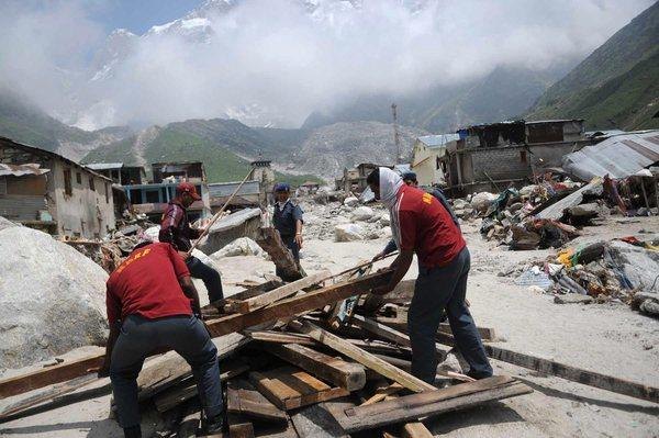Rescue workers prepare wood for mass cremations near Kedarnath Shrine in India's flood-ravaged state of Uttarakhand. Authorities say the death toll from days of flooding has topped 820.