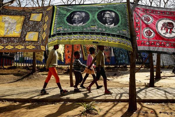 Children in Johannesburg, South Africa, pass by a souvenir flag of former President Nelson Mandela. Mandela, 94, is hospitalized in critical condition, and President Obama will defer to his family on whether he should pay a visit during his Africa tour.