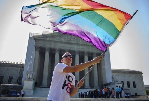 A same-sex marriage supporter waves a rainbow flag in front of the U.S. Supreme Court on Tuesday.