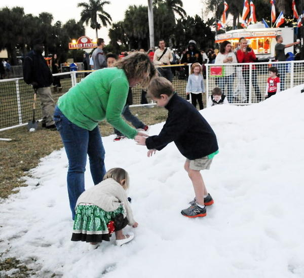 Boca's annual holiday tree-lighting event last year included snow, a live ice sculpture demonstration, children's rides and fireworks. here, Wendy Fincher of Boca plays with her children, Reese, 2, and Christopher, 5.