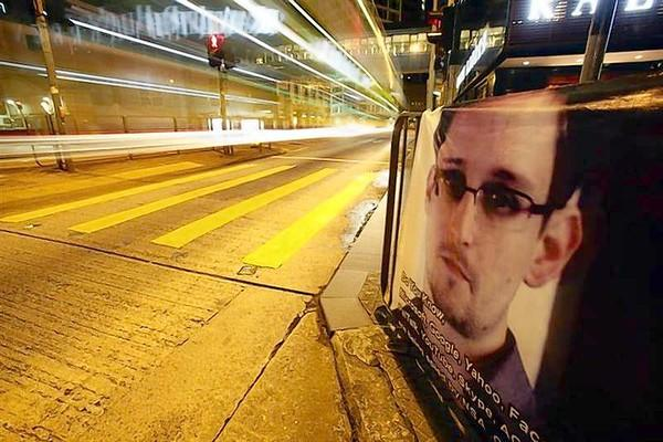 A bus passes by a poster of Edward Snowden in Hong Kong.