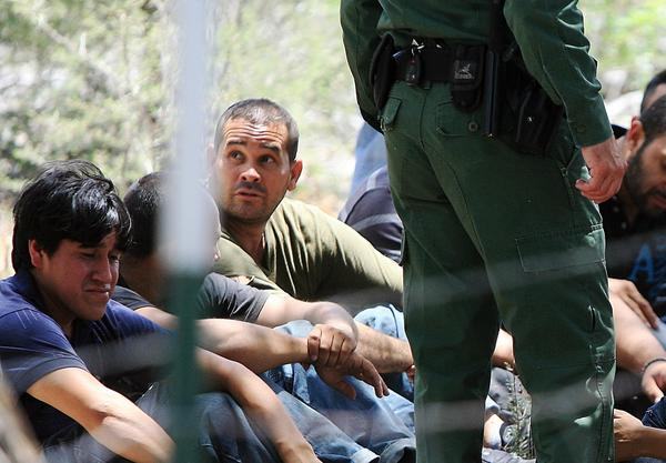 "Many feel that the ""border surge"" approach to immigration, which would double the size of the Border Patrol and mandate more fencing, is a waste of taxpayer dollars. Above: In a field in Edinburg, Tex., Border Patrol agents watch over 69 people suspected of entering the country illegally."