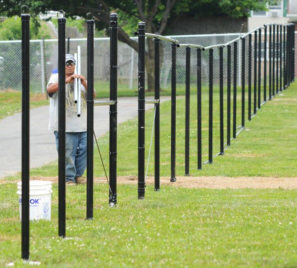 Jose Maldonado installs a 6-foot chainlink fence to prepare for Saturday's grand opening of the the new Hagerstown Dog Park at Fairgrounds Park. The park will have two separate fenced in areas, one for small dogs and large dogs and each side has a pavillion, drinking fountains, hydrants and benches.