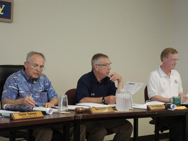 Boyne City Mayor Ron Grunch (from left), commissioner Thomas Neidhamer and city manager Michael Cain listen to Boyne Mountain Director Ed Grice present information on a sewer line expansion and other improvements planned for the resort at the Boyne City Commission meeting Tuesday.