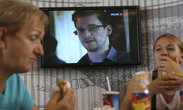 Passengers eat at a cafe in Moscow's Sheremetyevo airport Wednesday with a TV screen showing a report on Edward Snowden, who is believed to be in the airport.