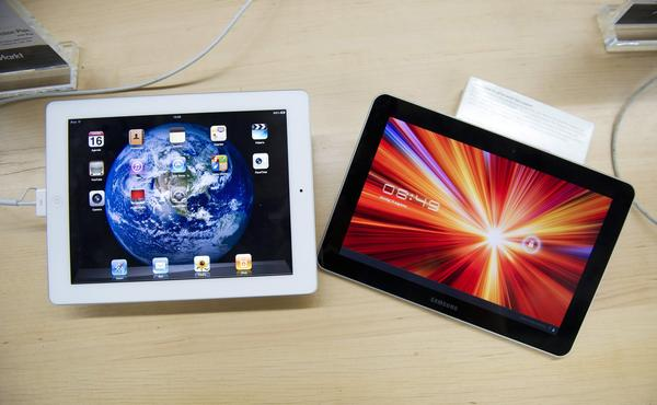 An Apple iPad, left, and a Samsung Galaxy Tab 10.1 at a store in The Hague, the Netherlands. Tablet owners say they know more about what's in the news than their tablet-less peers, according to a survey.