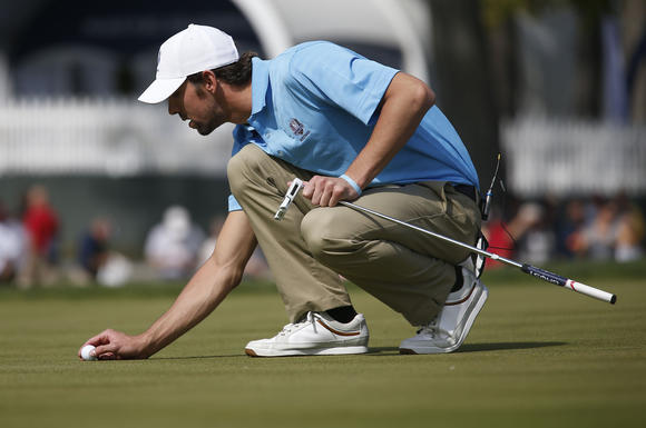 Michael Phelps sets his ball on the green on the first hole in the Captain/Celebrity Pairings at the Medinah Country Club last fall. (José M. Osorio/Chicago Tribune)